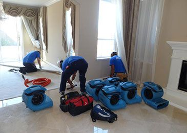 Water damage restoration team cleaning up a house