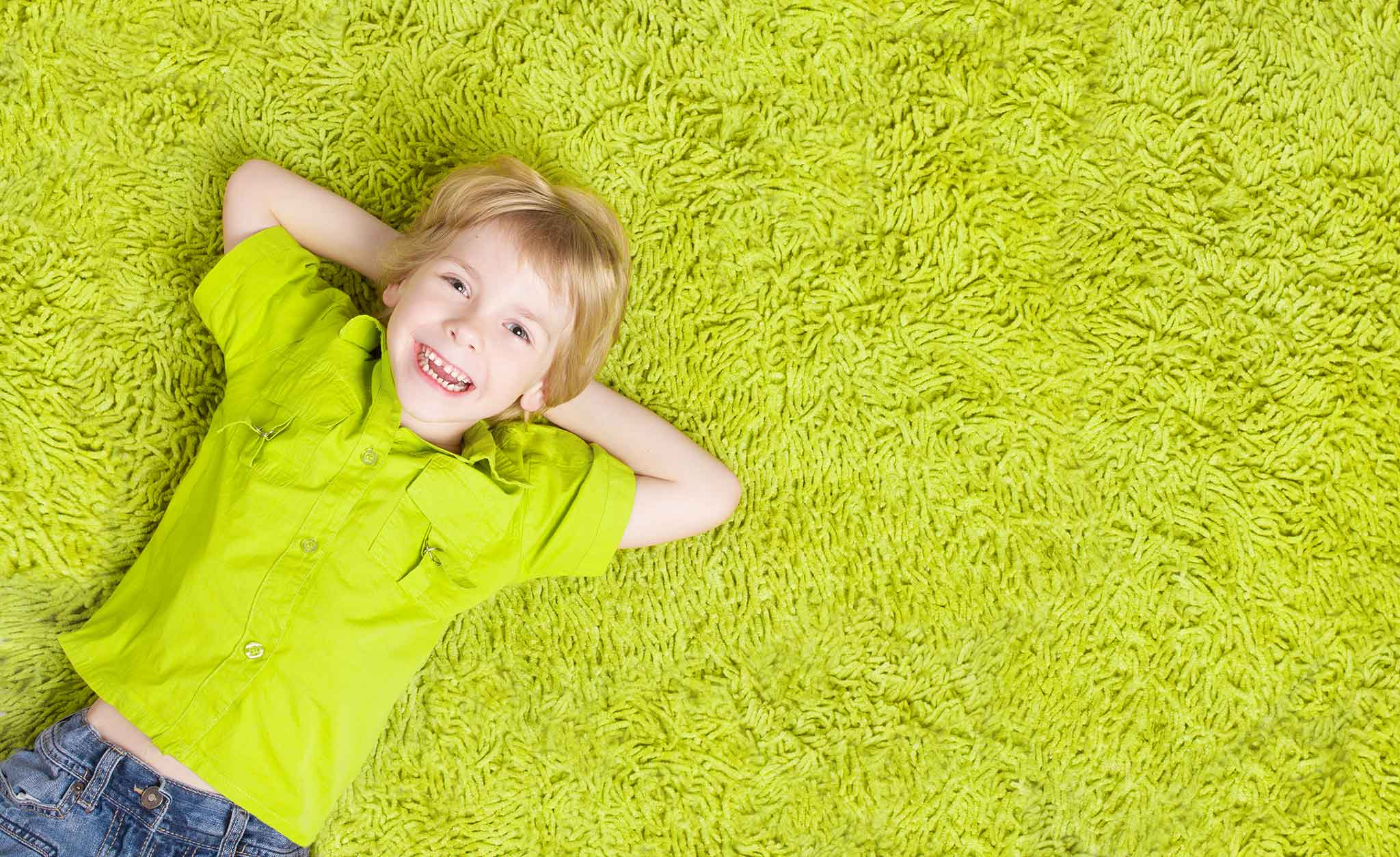 Happy baby smiling and laying on a rug